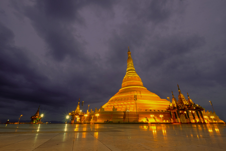 Golden color Uppatasanti pagoda in Nay Pyi Taw capital , Myanmar, in the evening with dramatic cloudy sky 版權商用圖片