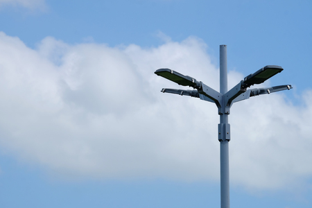High electrical light pole on cross shape with background of big white cloud on blue sky day