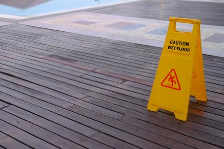 Caution Wet Floor warning yellow sign on wooden floor beside swimming pool