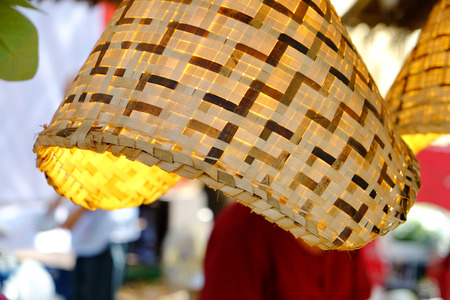 Rattan wicker lamp hanging with the light inside is getting on