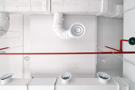 Bottom view of white air duct on the ceiling with red water sprinkler pipe and