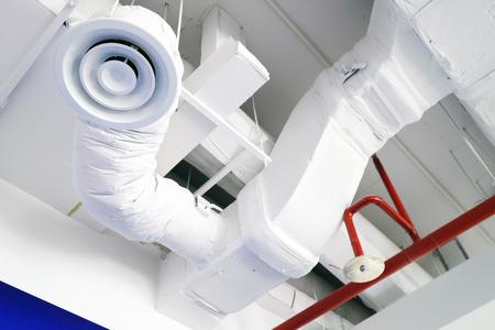 Vista rialzata del condotto dell'aria bianco sul soffitto con tubo irrigatore ad acqua rossa Archivio Fotografico