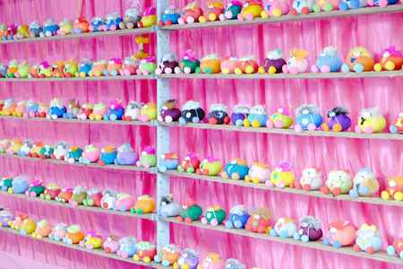 Perspective view of many dolls in multiple rows on the shelf