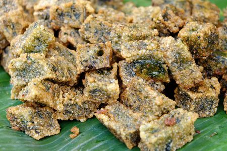 Pile of deep fried garlic chives dumpling food on fresh banana leaf