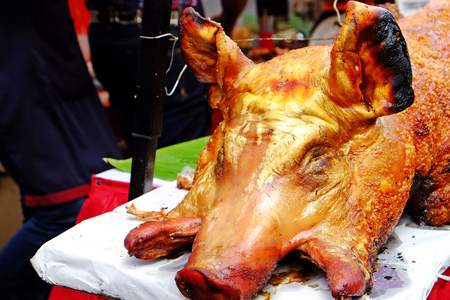 Entire head of barbecued suckling pork, cooked by grilling, crispy and roasted, prepared to serve for meal