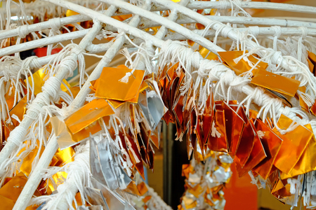 Silver and gold color glossy paper tied with white thread hanging in funfair for lucky draw game