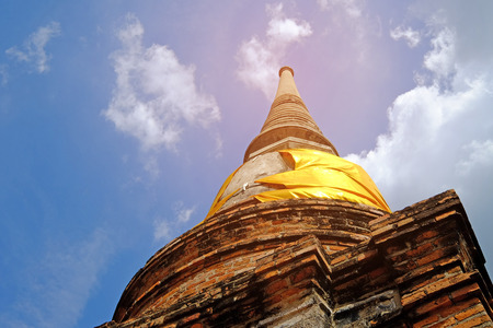Worm eye view of old big pagoda made by bricks and concrete, covered by shiny yellow robe of Buddhist monk