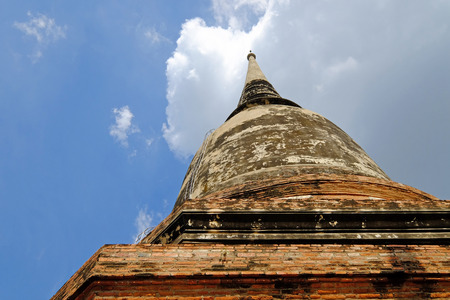 Worm eye view of big old Buddhism pagoda on cloudy blue sky background Stock Photo