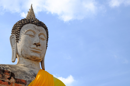 Worm eye perspective view Lord Buddha statue, closeup on head part, outdoor, on the cloudy blue sky background, with copy space Stock Photo