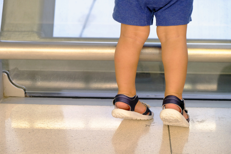 Legs of small kid, wearing blue shorts, doing tiptoe on the ground floor near the window