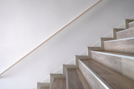 Side view of wooden stairs and handrail attached to the wall Stock Photo