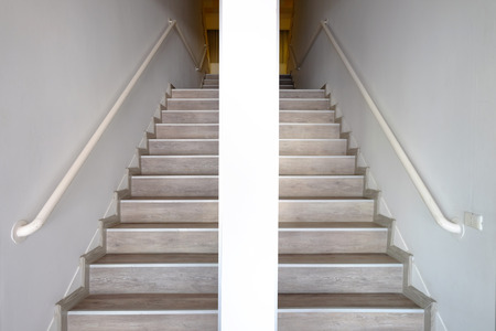 Symmetry wooden stairway on left and right with handrails attached to the walls and pillar in the middle Stok Fotoğraf