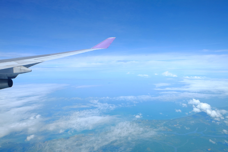 Wing of airplane above the sky over a cloudscape, natural green island and blue ocean Stock Photo