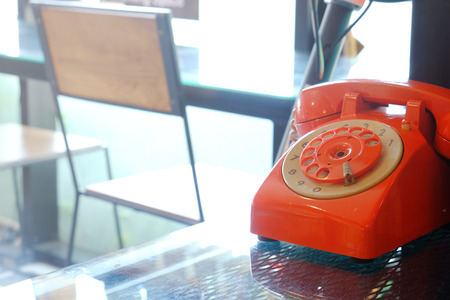 Old fashioned fixed line orange rotary phone on glass table