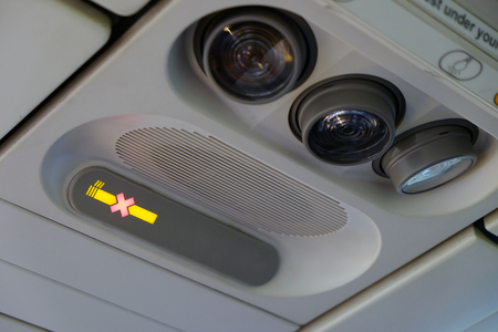No smoking sign on the overhead information panel in the airplane