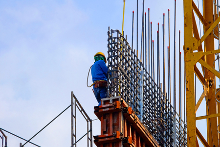 Foreman worker in safety uniform working on construction site with copy space
