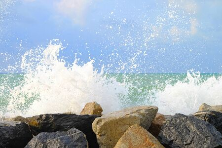 Water wave hit stone wall and made instant bubble foam on the shore Imagens