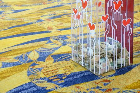 Transparent donation box filled with some banknotes on carpet floor