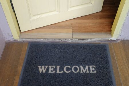 Black welcome doormat carpet in front of the opening door