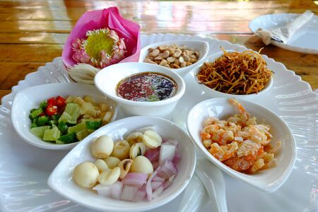Royal leaf wrap appetizer, AKA Miang Kham in Thai, local traditional style food, prepared and served separately in white plate on wood table