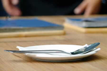 White dish and spoon with fork arranged on wood table, with menu book in background