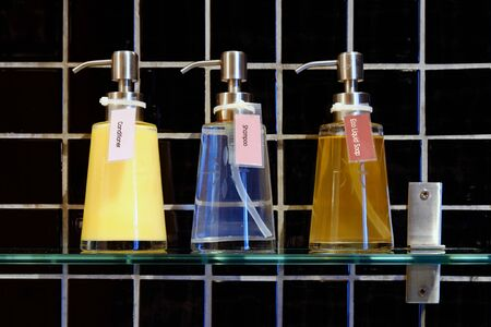 Liquid soap, shampoo and conditioner in three clear pump bottles on a shelf with background of black tiles Stockfoto