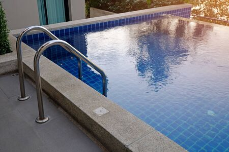 Swimming pool with metal ladder, outdoor nearby the house Foto de archivo