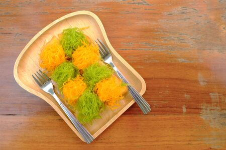Sweet golden egg and green pandan thread dessert over baked bread on wood tray, ready to serve with two forks