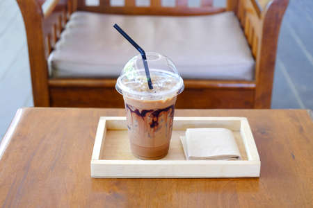 Iced chocolate marble drink served in plastic glass in a wood tray with tissue paper on table