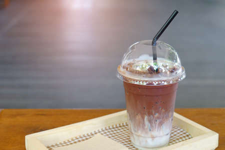 Iced milk chocolate drink served in plastic glass on wood table