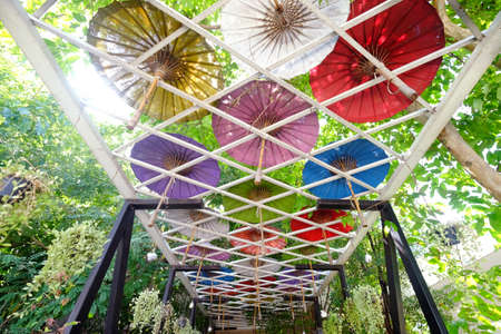 Metal arch and beautiful colorful Japanese paper umbrella on the top in green garden