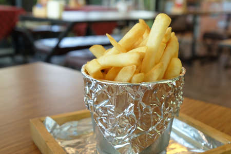 Crispy French fries served in a bucket on table in a restaurant