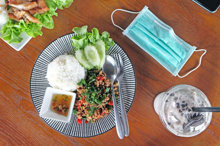 Top view spicy dish of fried minced pork with sweet basil leaf and rice, served with drink, and surgical mask on wood table