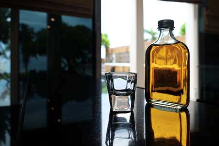 Silhouette bottle of liqueur and short shot glass on reflected surface bar