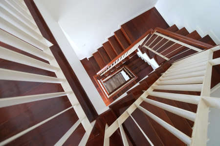 Top view spiral wood stairs with handrails to the ground floor