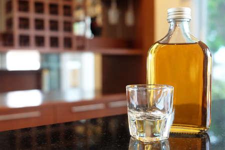 Bottle of liqueur and short shot glass on shiny surface bar Foto de archivo