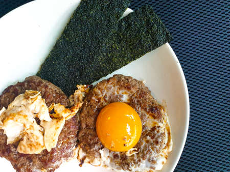Breakfast of grilled meat burger and fried egg on top with crispy seaweed on white dish and copy space for vertical Japanese characters on the right side