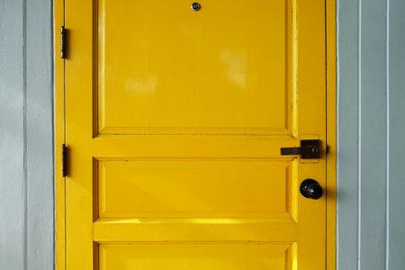 Closeup yellow wood door with doorknob and peephole