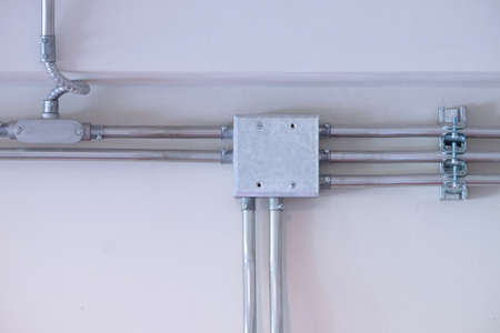 Steel conduit box and pipes installed on white wall