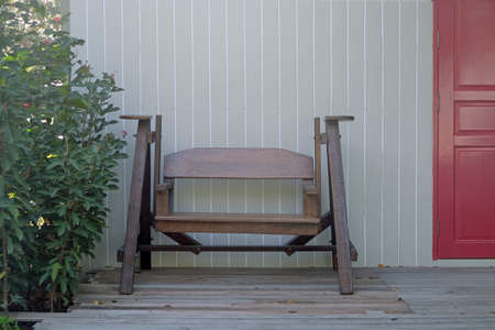 Wooden swinging chair in front of wood house wall