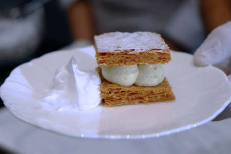 Snack made by baked bread, cream, and icing sugar in white plate prepared by chef