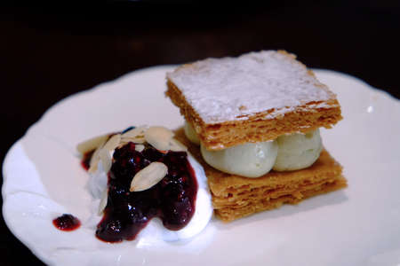 Snack made by baked bread, cream, blueberry, and icing sugar on white plate