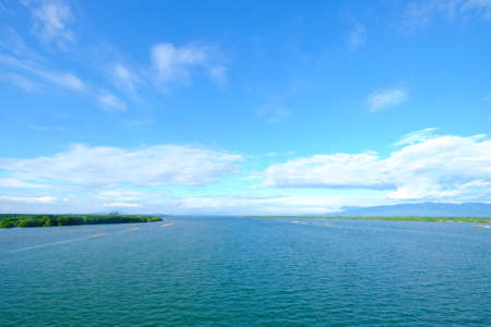 Beautiful landscape estuary of a river where the water meets the cloudy blue sky