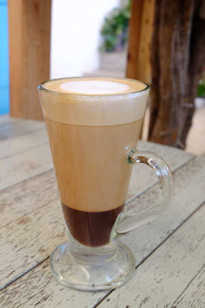 Hot mocha drink served in chocolate and coffee layers, in tall glass with handler on old wood surface table