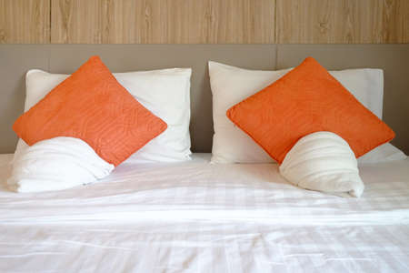 Bed set with white and orange pillows, blanket, bedsheet, and head board Foto de archivo