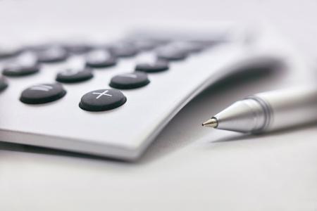 macro photograph of a pen and a calculator