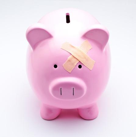 Piggy bank with bandage Illustrating money problems photo
