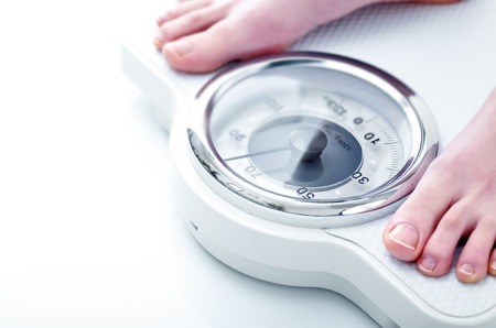 Photograph showing the feet of a woman on a bathroom scale close-up Stock Photo