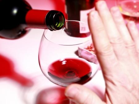 Fotografía de detalle que muestra el enfoque del consumo de alcohol en el cuello de la botella y una copa de vino; Foto de archivo