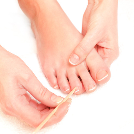Photography of a woman pushing cuticles toes
